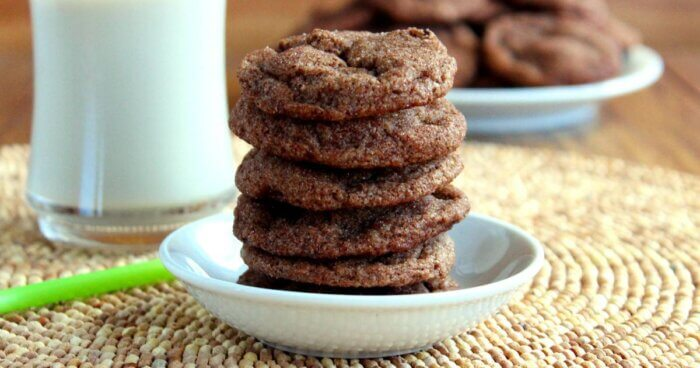 Wide photo of double chocolate chip cookie recipe, milk and more cookies on a wooden mat.