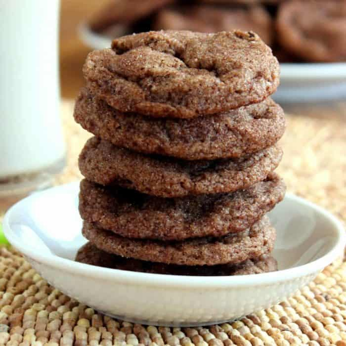 Square photo of a stack of vegan double chocolate chip cookies in a small white bowl.
