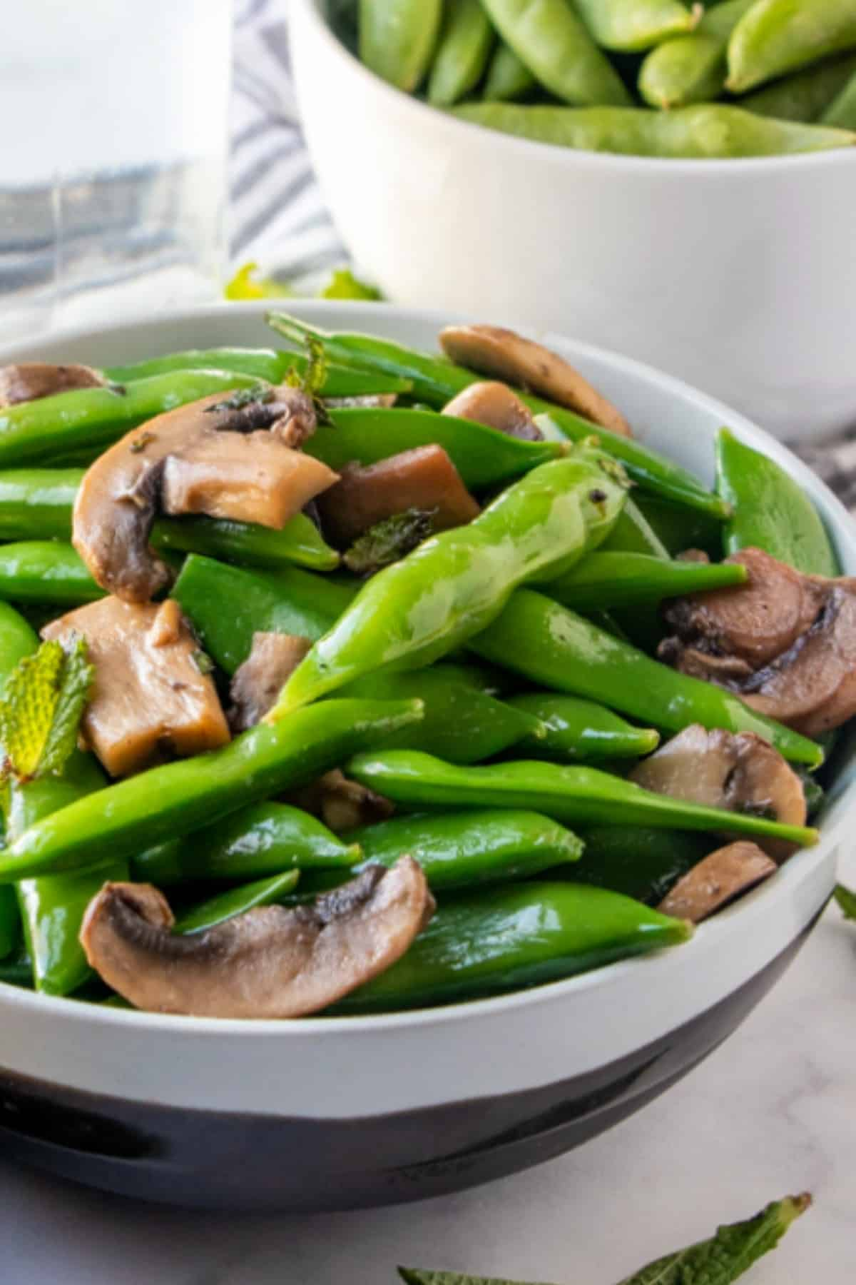 Close up view of glistening a sugar snap peas recipe with mushrooms in a white and silver striped bowl.