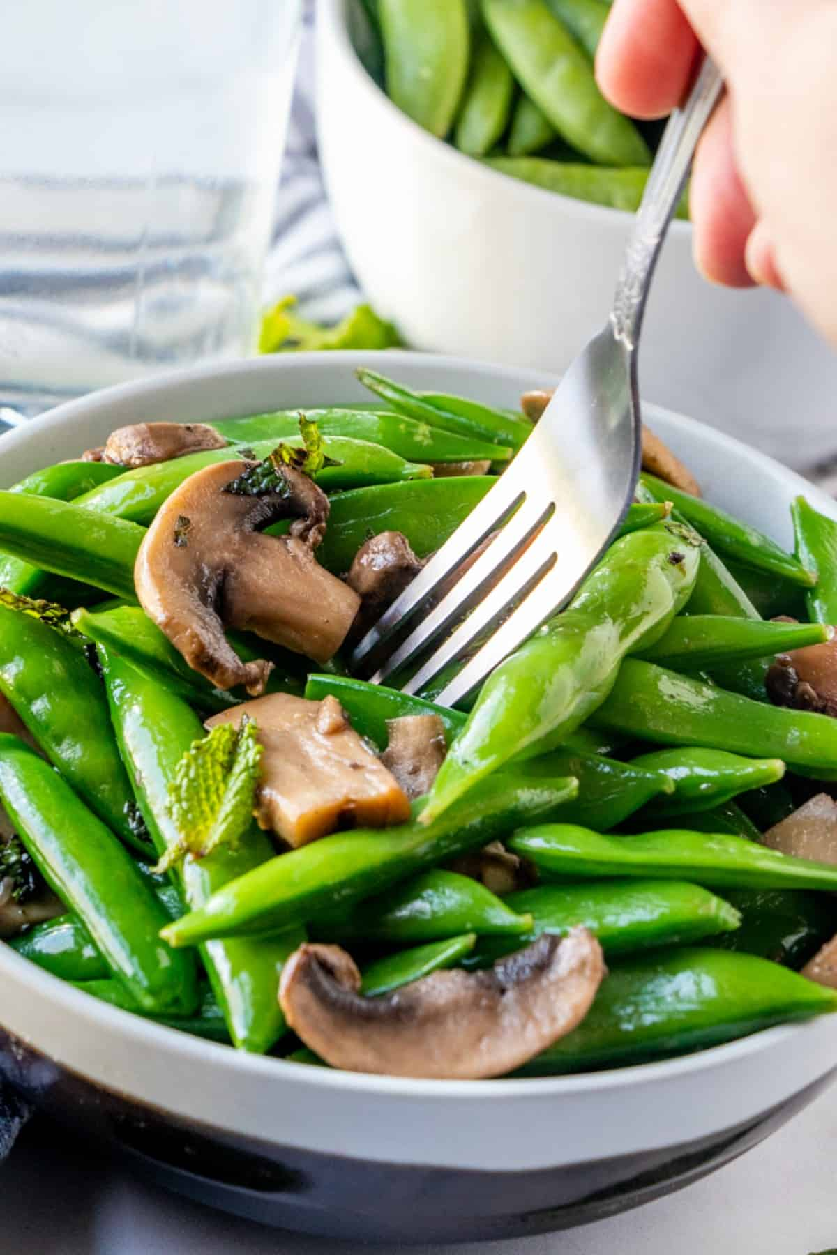 Angled bowl full of sugar snap peas with a fork pulling up the first bite.