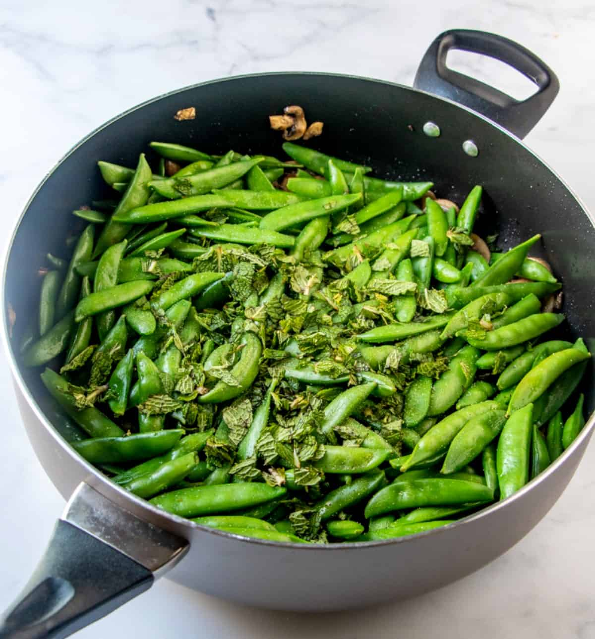 Sugar Snap peas are added in the skillet along with fresh mint.