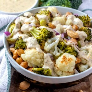 Roasted vegetables tossed in a white bowl and covered with creamy sauce.
