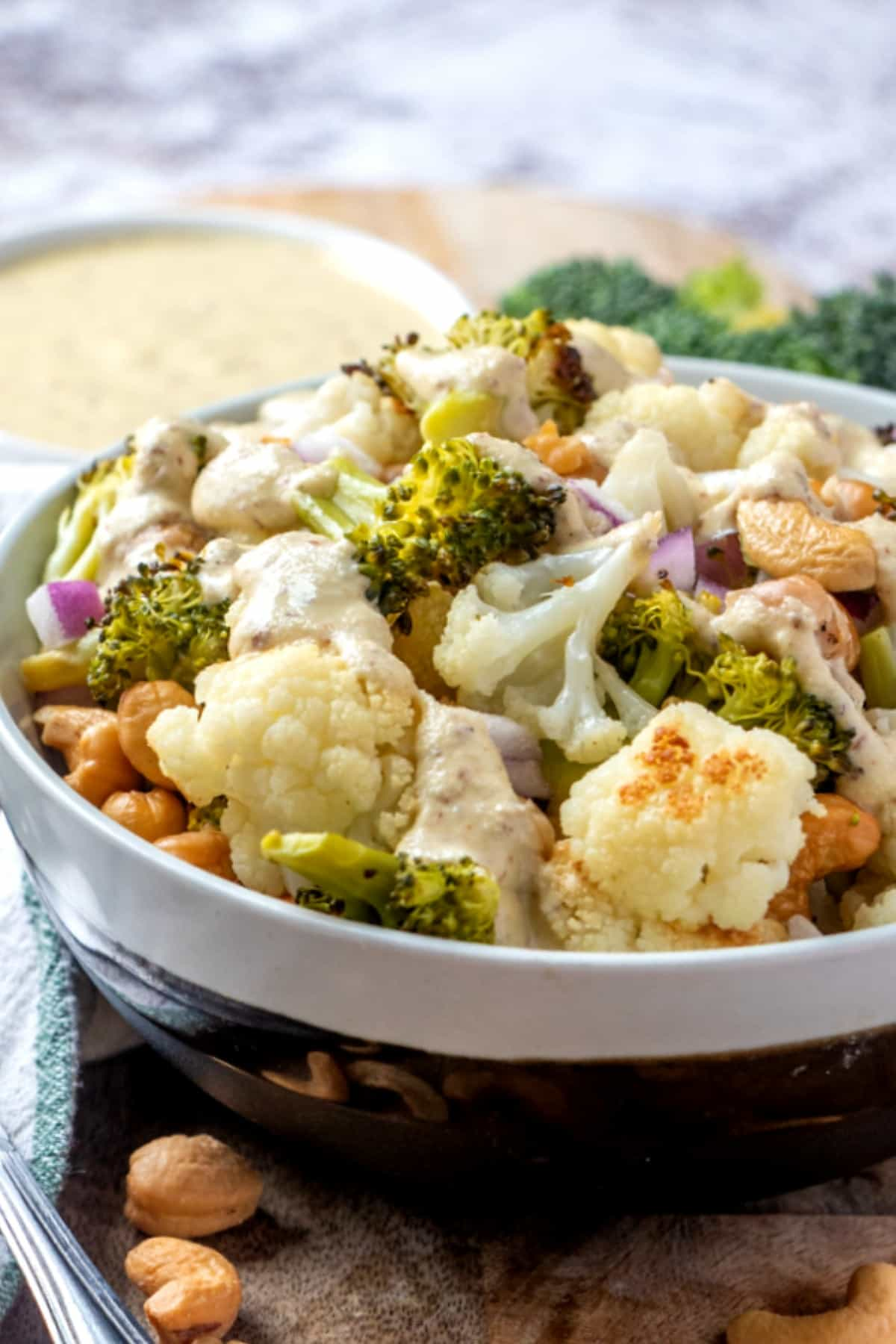 Cropped vegan Buddha bowl full of roasted veggies with a sauce over the top and cashews sprinkled around the sides.