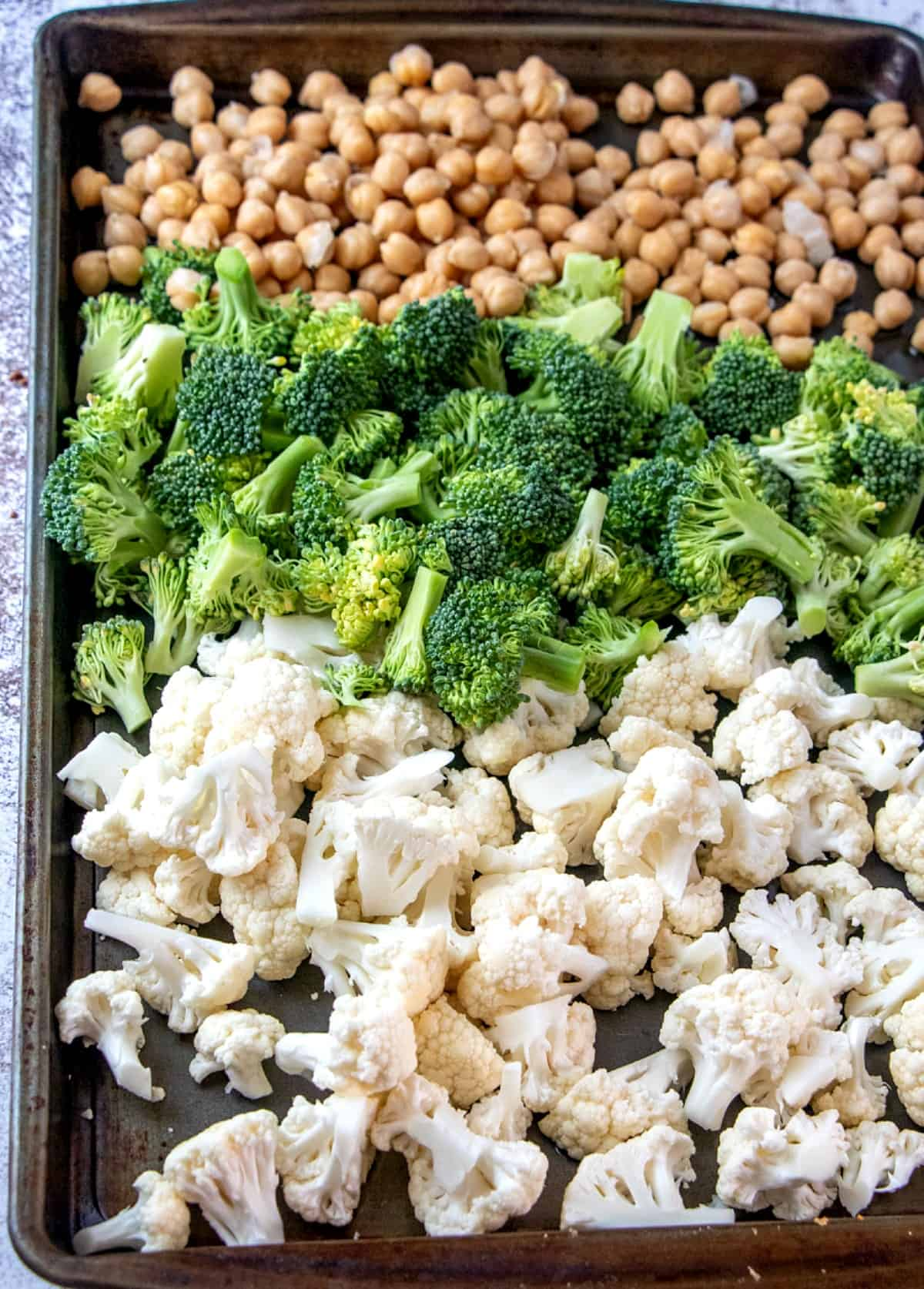 Cauliflower, broccoli and chickpeas are lined up on a baking sheet and ready to be roasted.