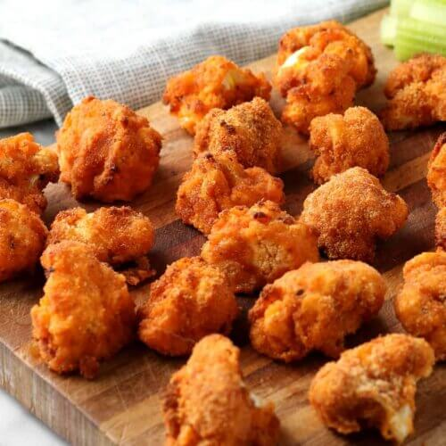 Close up square photo of multiple cauliflower buffalo bites strewn across a wooden cutting board.