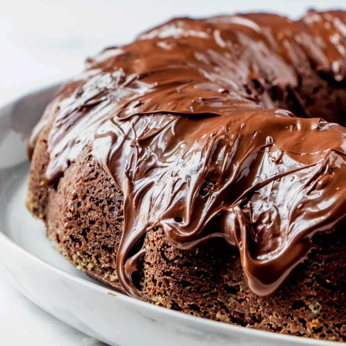 Close up photo of half of a chocolate bundt cake with thick frosting drizzled over all the nooks and crannies