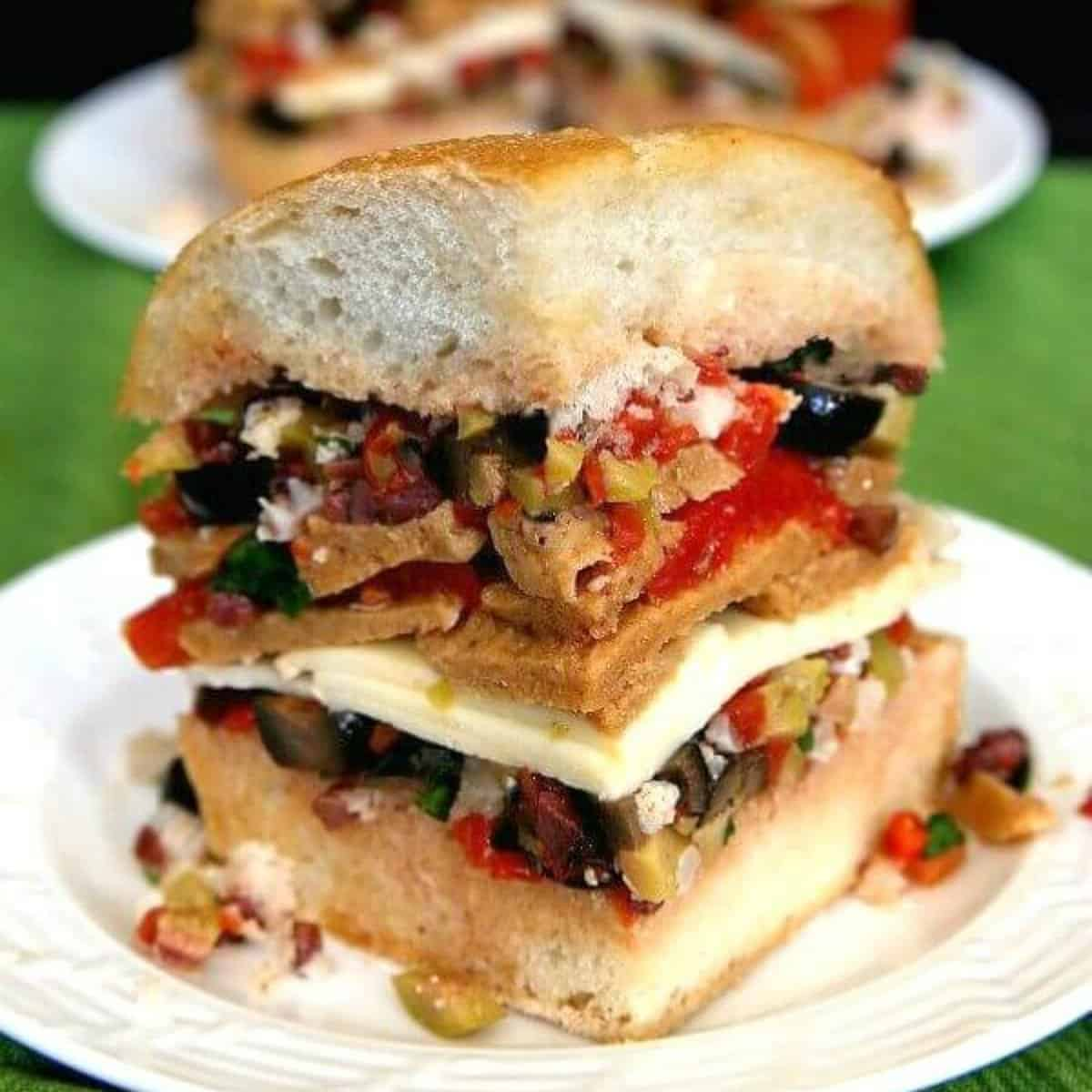 Wedge slice of piled high layered sandwich on a white plate.