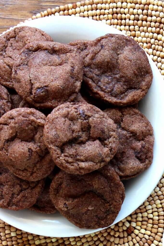 Overhead photo of a spread of vegan double chocolate chip cookies on a white plate against a wooden mat.