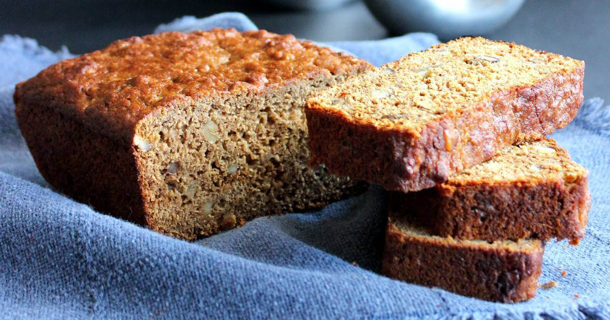 Wide photo of a loaf of pear bread with slices stacked along side.