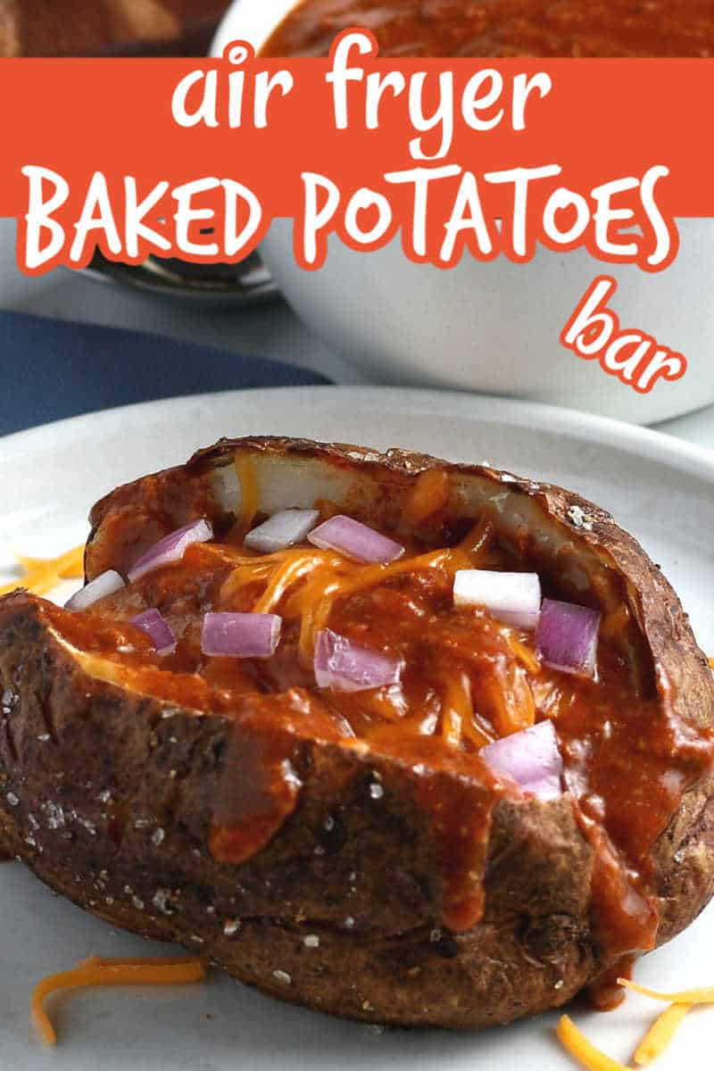 A tilted view of a split open baked potato with chili ladled down the middle and sprinkled with diced red onions and dairy-free cheddar cheese. Text above for Pinterest.