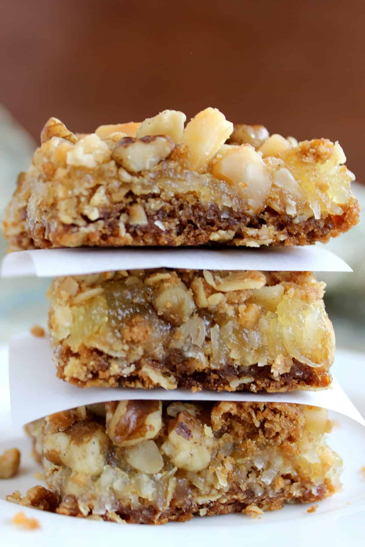 Extreme close up of three pina colada bars Stacked on top of each other with creamy yellow jam centers, oat bottoms and nut tops.
