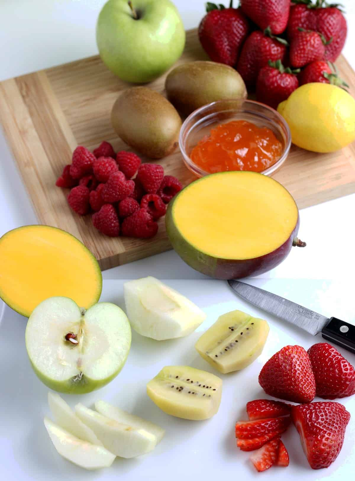 Fruit varieties being diced and sliced on a wooden cutting board with some halves in front.