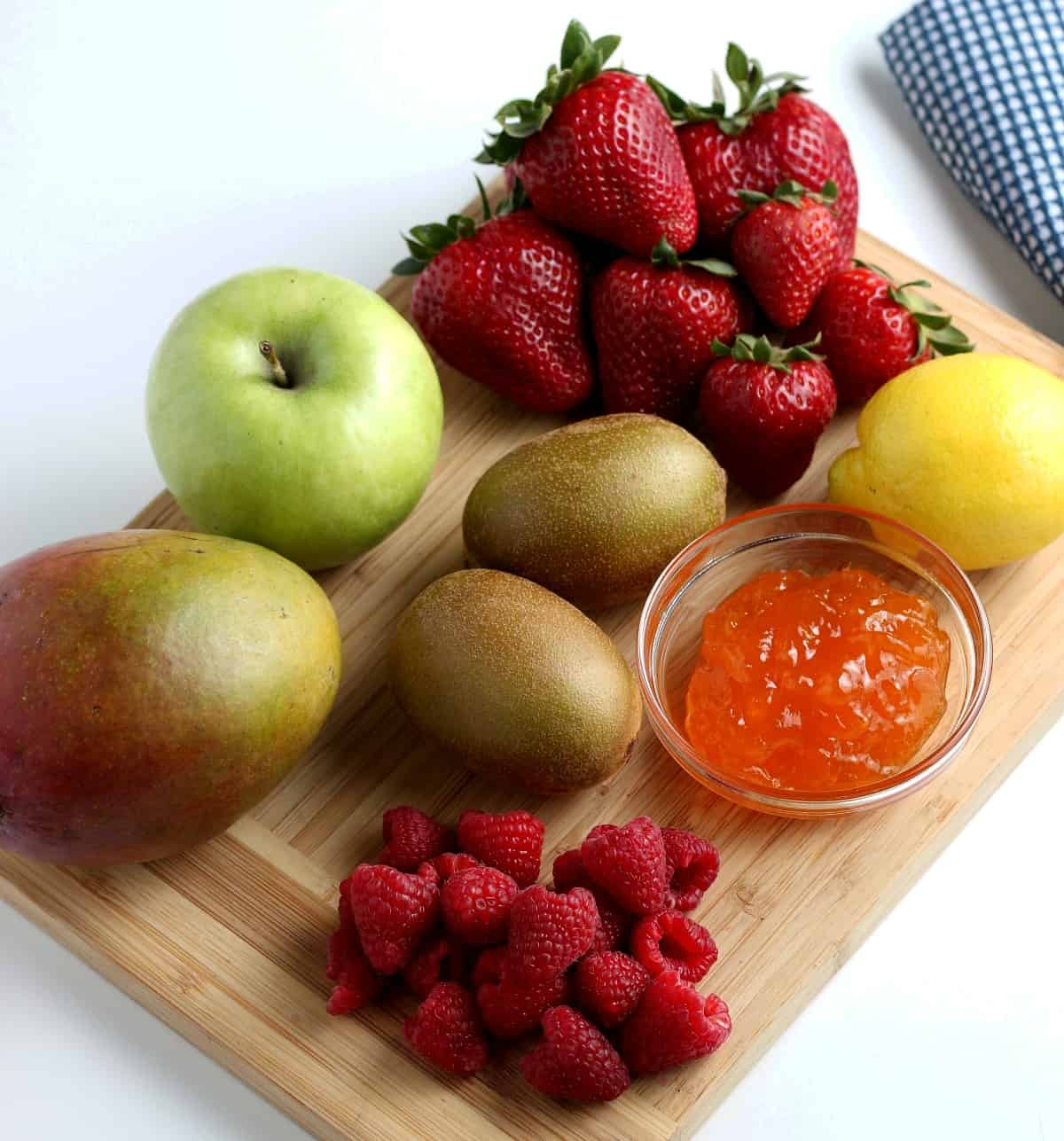 Overhead view of piles of 6 different fruit varieties on a wooden cutting board.