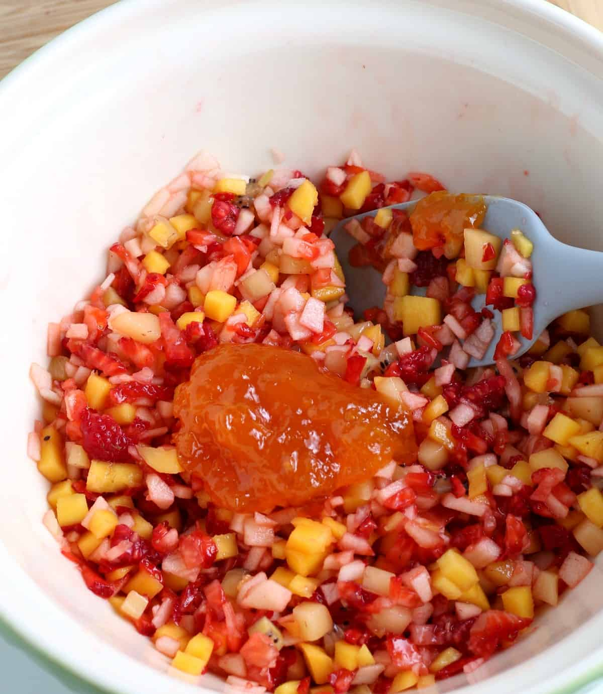 Marmalade is dolloped in the center of freshly diced fruit so that it can be tossed in the bowl.