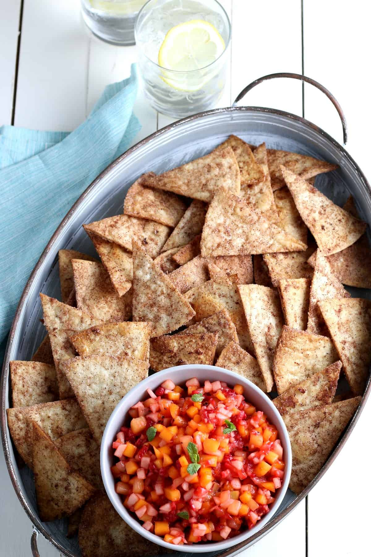 Overhead photo of a handles tray full of cinnamon chips and a bowlful of read and orange fruit salsa.