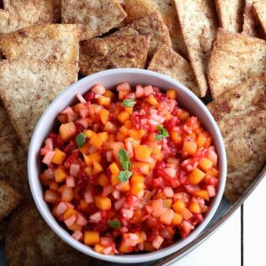 Overhead photo of small diced fruit tossed together, in a small bowl and surrounded with cinnamon chips.