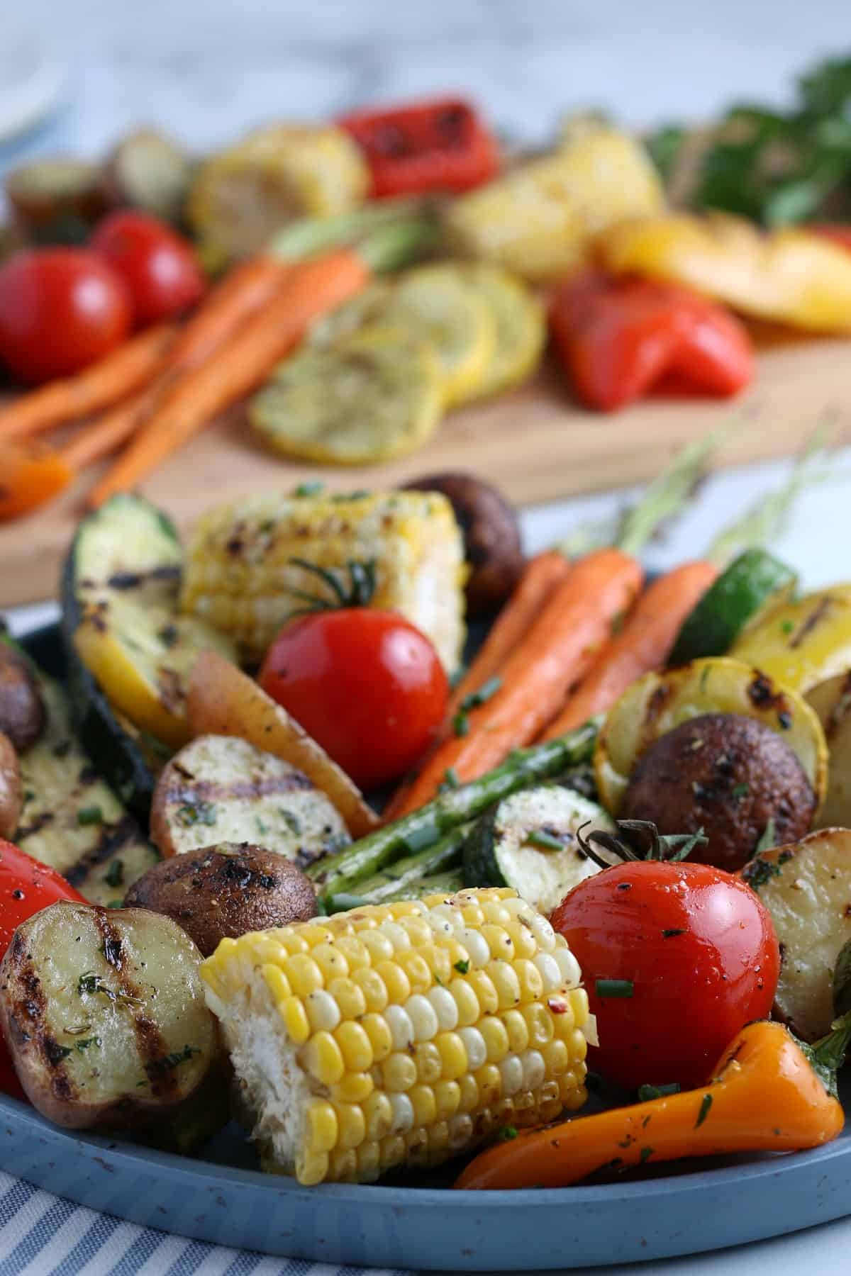 A closeup photo of mixed whole grilled vegetables on an enamelware platter with more behind on a wooden cutting board.