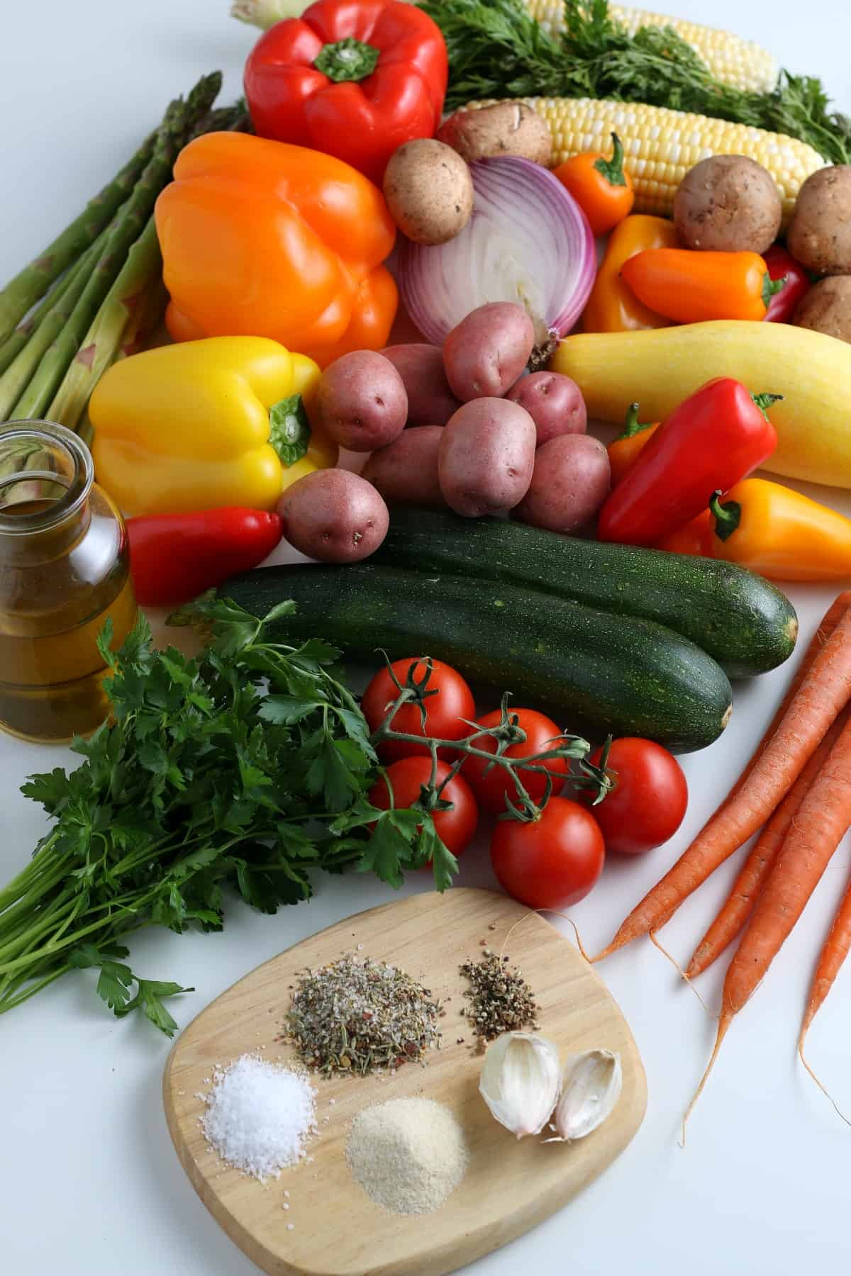 Overhead view of a colorful array of fresh vegetables and marinade ingredients against a white background..