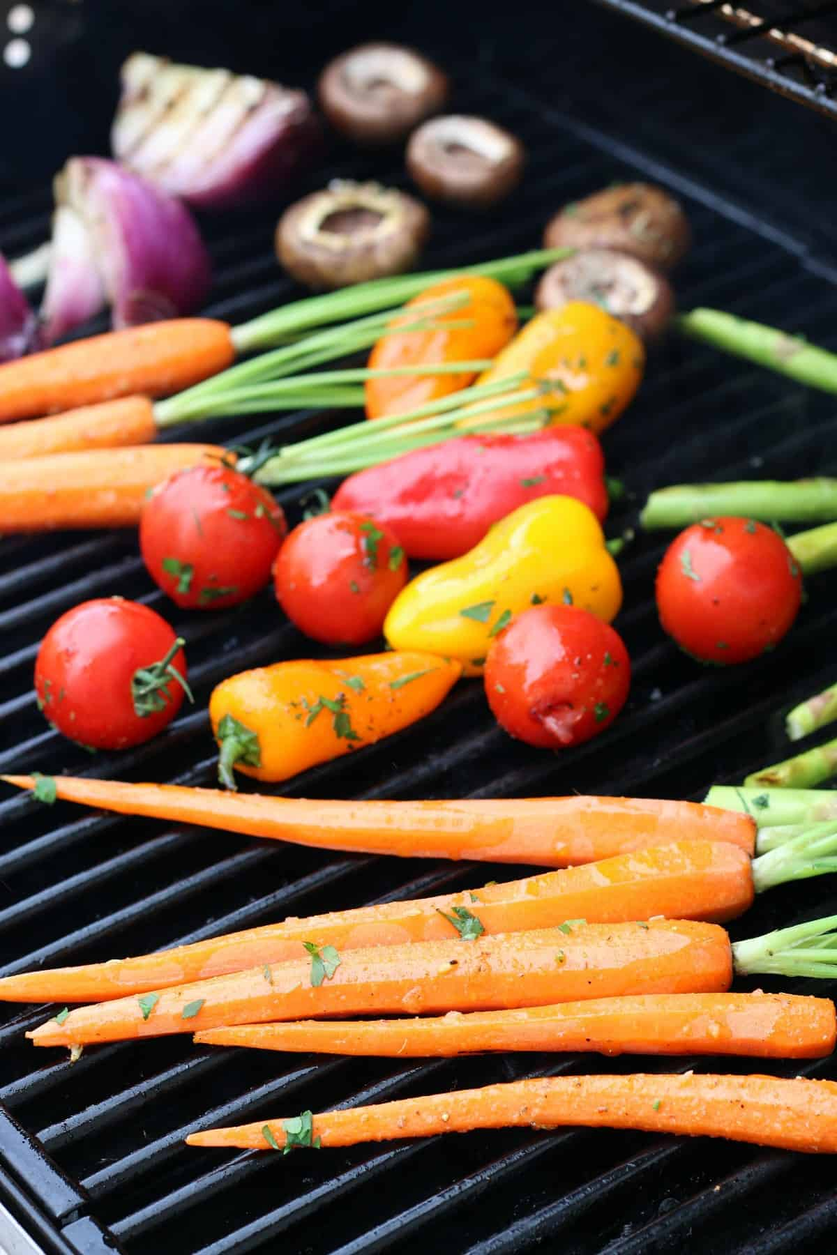 Whole and cut fresh vegetables are brushed with a grilling mix and are laying across the top of a grill.