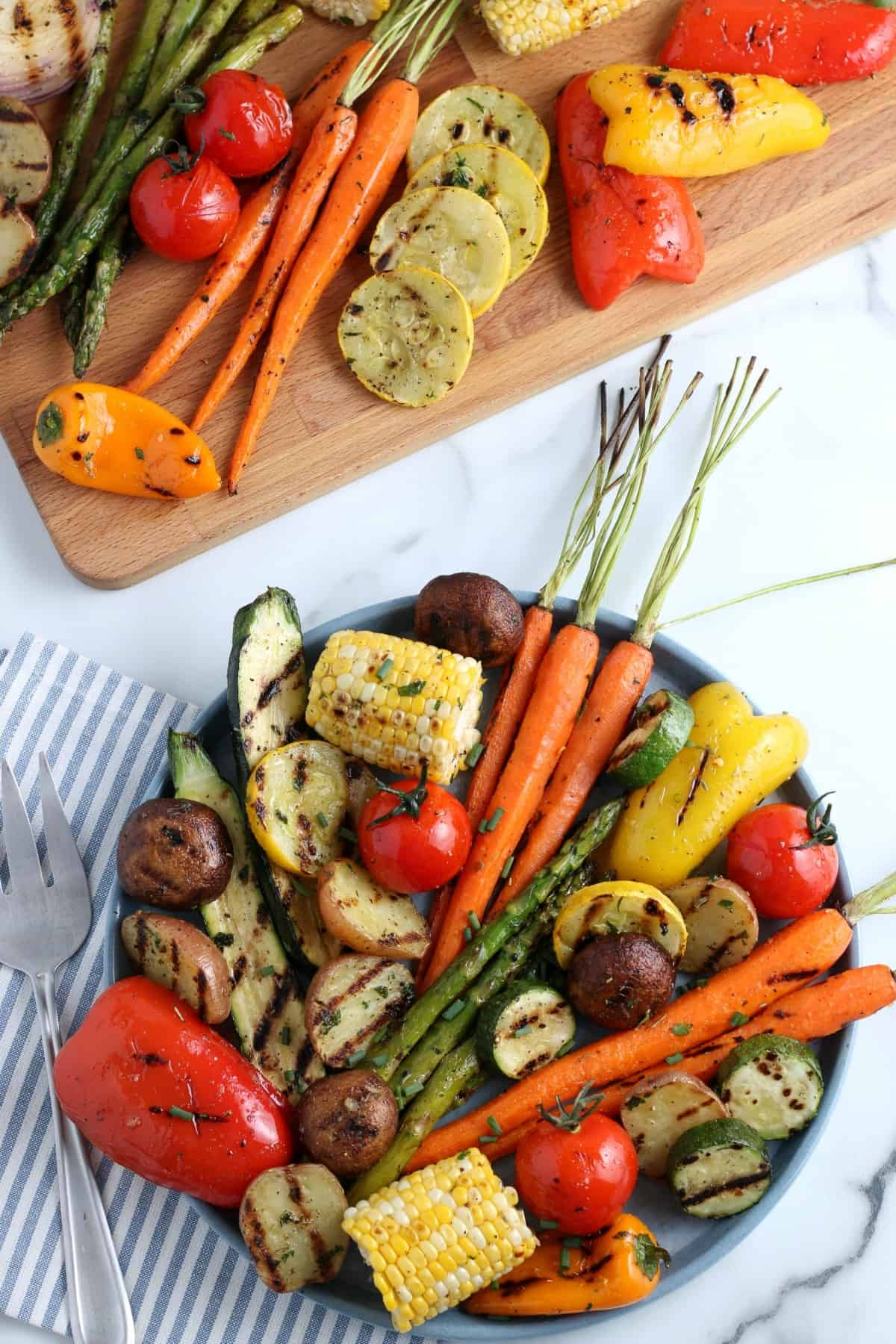 Overhead view of whole and sliced grilled vegetables mixed together on a large serving platter.