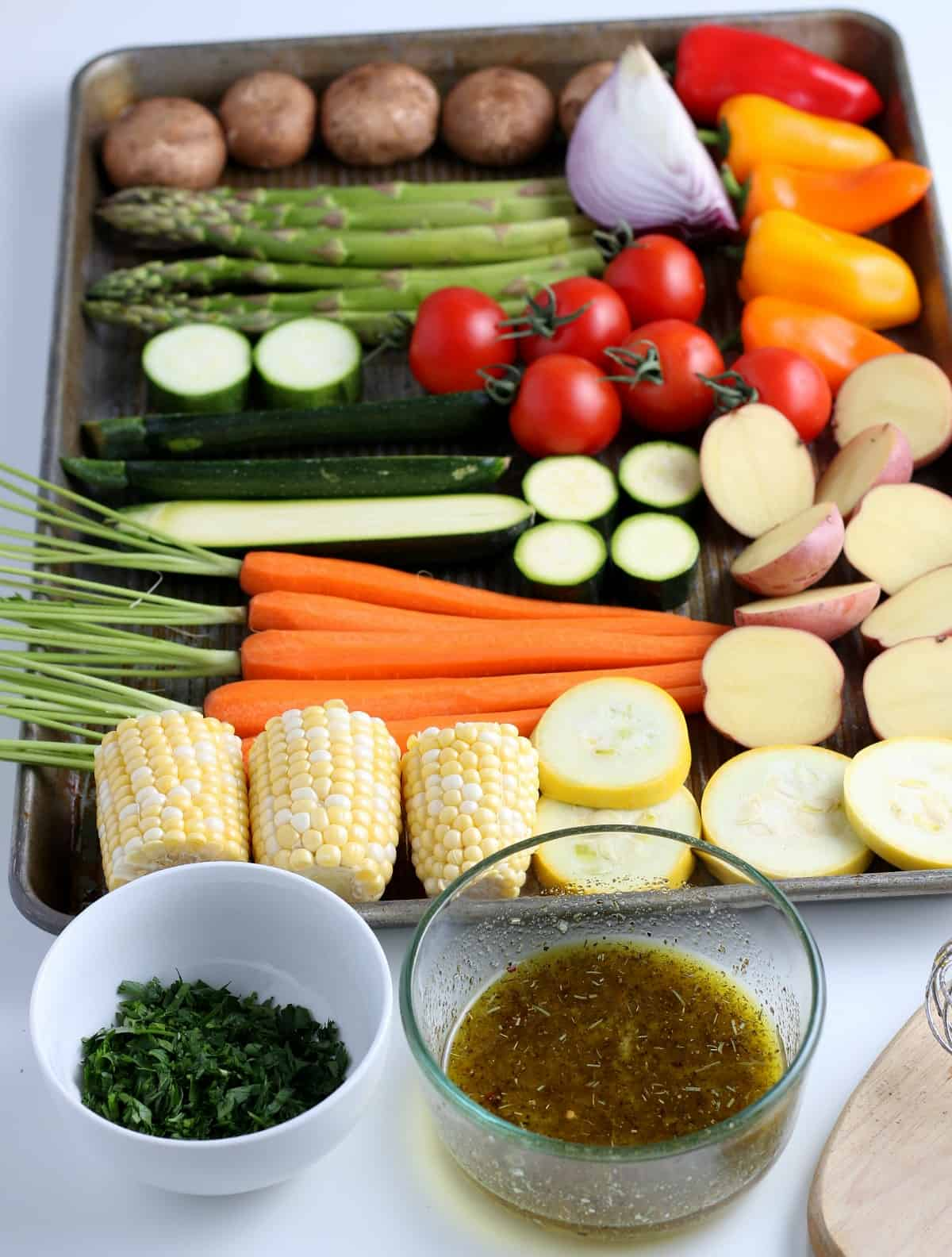 Slanted view of prepared vegetables laid out on a sheet pan with marinade and fresh parsley in front.