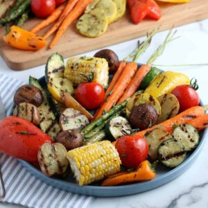 Close angled enamelware platter filled with grilled vegetables with more behind on a wooden board.