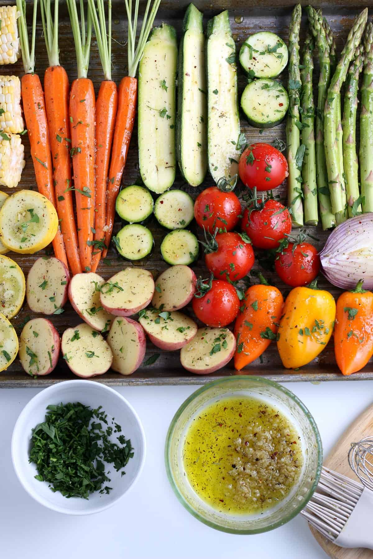 Overhead view of all of the fresh prepared vegetables laid out on a sheet pay and brushed with the grilling marinade.