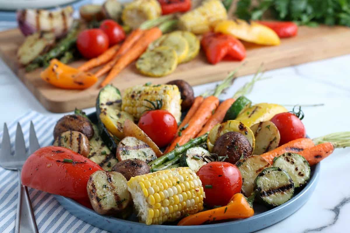 Wide angel platter full of grilled vegetables on a striped cloth napkin.