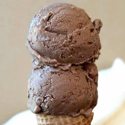 Two big scoops of vegan chocolate ice cream on a sugar cone.