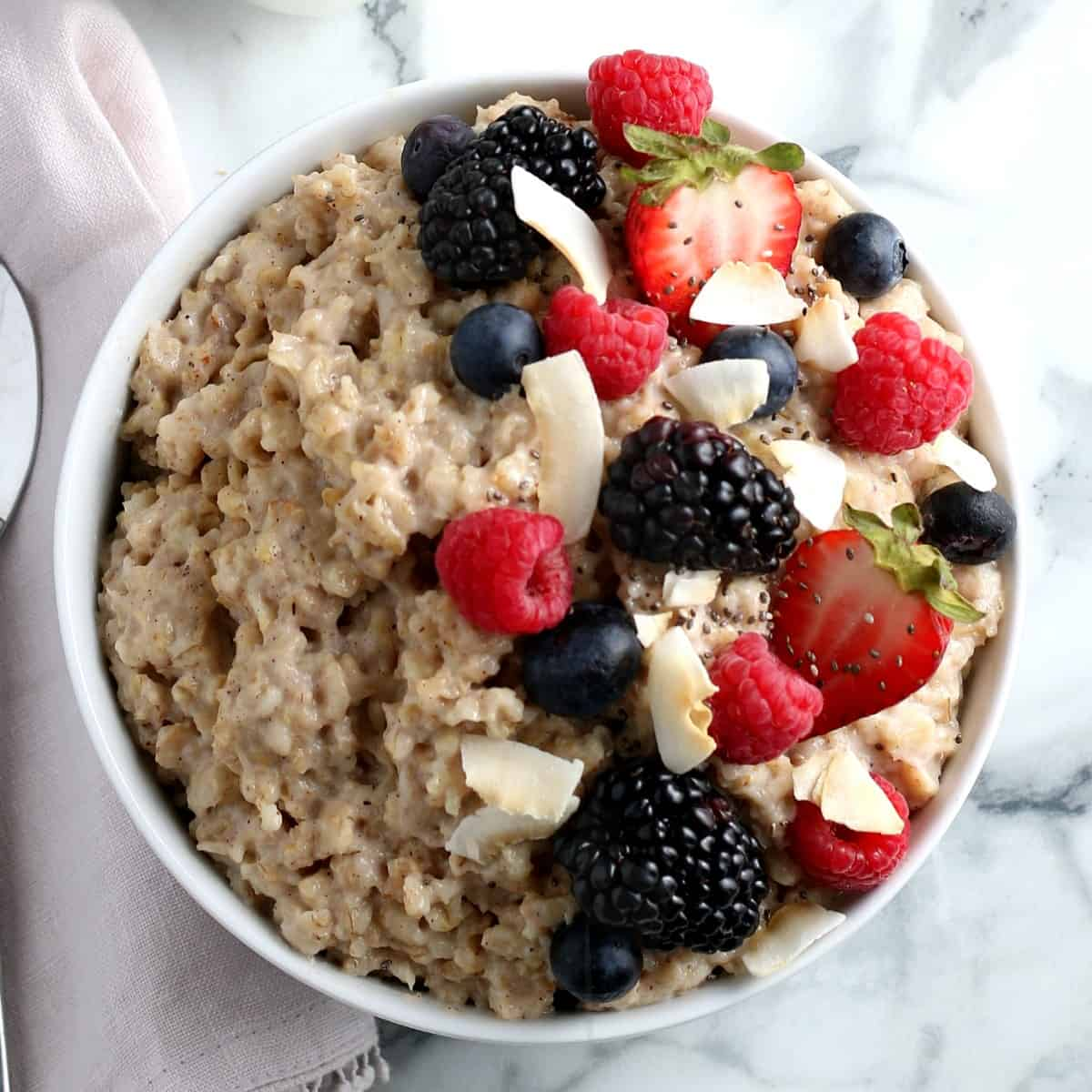 Overhead view of Oatmeal with half the bowl covered with fresh berries and coconut flakes.