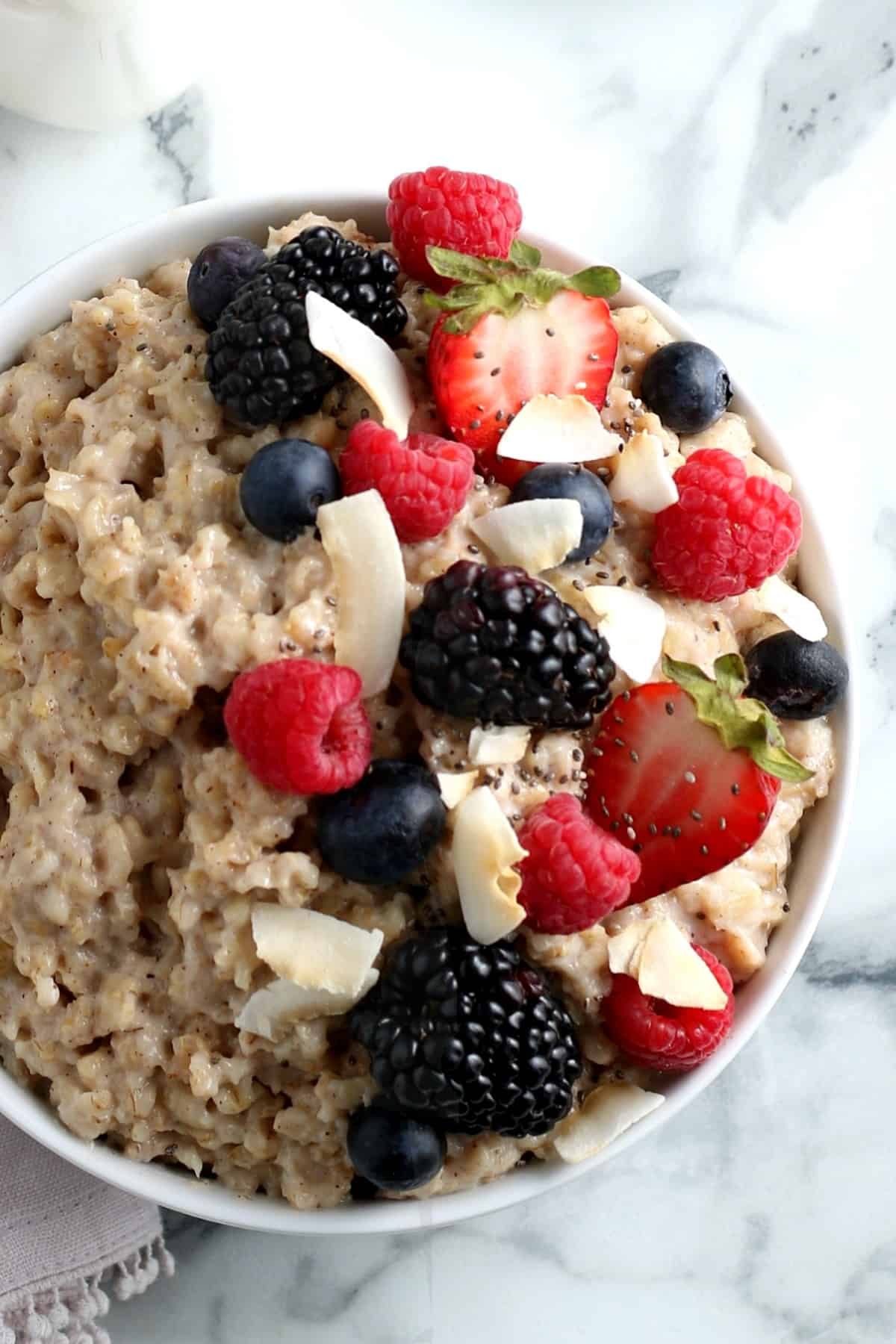 Overhead closeup of a cropped white bowl of oatmeal scattered with colorful berries.