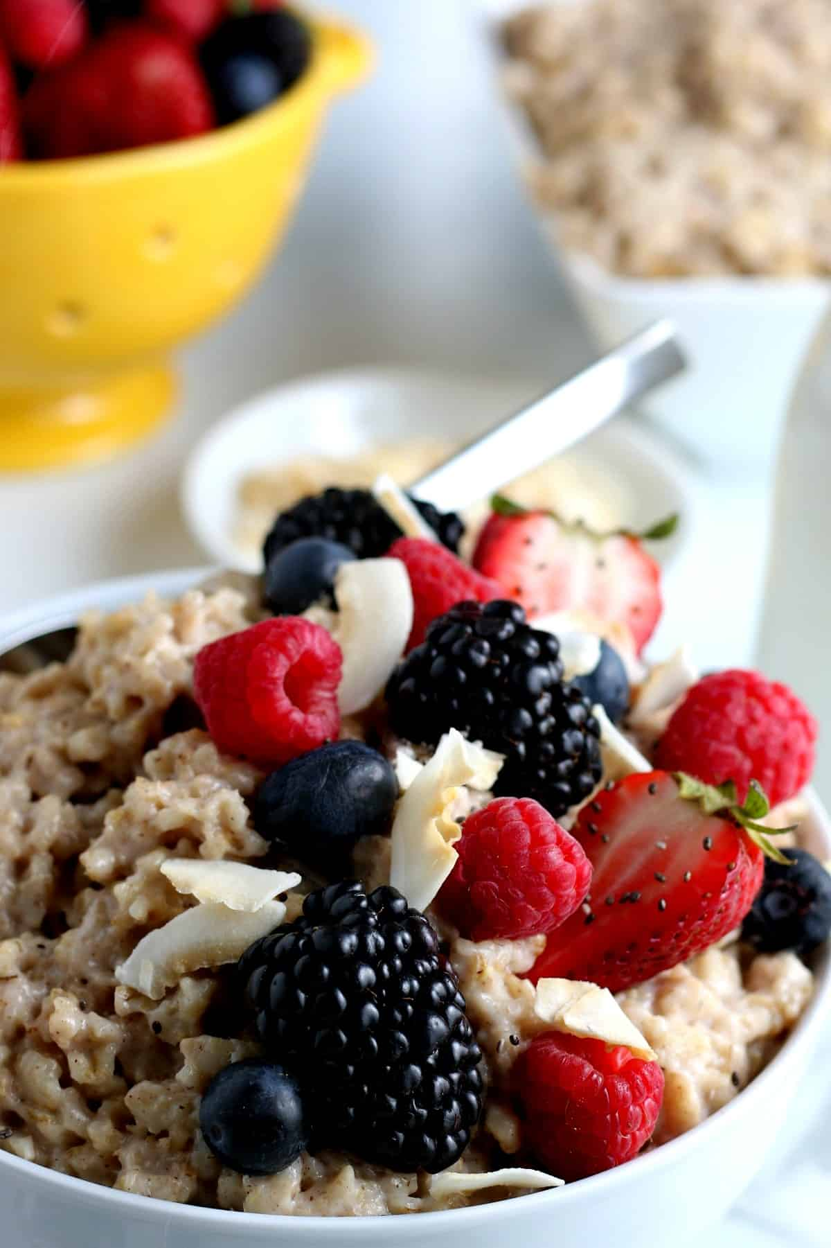 Super closeup photo of oatmeal in a bowl with black and red berries over the top.