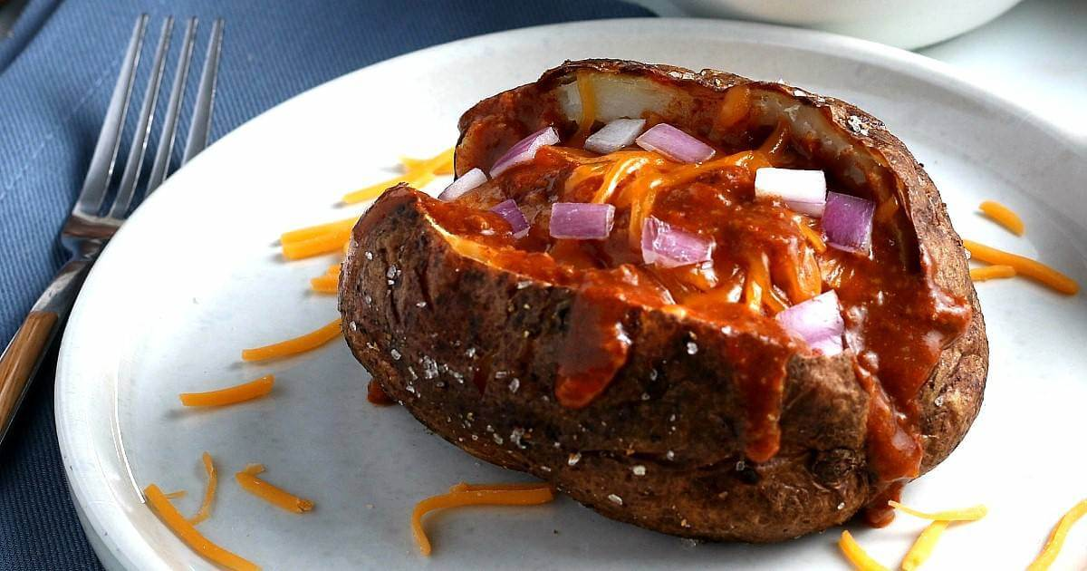 A tilted view of a split open baked potato with chili ladled down the middle and sprinkled with diced red onions and dairy-free cheddar cheese.