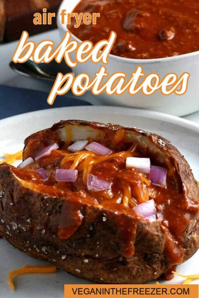 A tilted view of a split open baked potato with chili ladled down the middle and sprinkled with diced red onions and dairy-free cheddar cheese. Text above for Pinterest pinning.