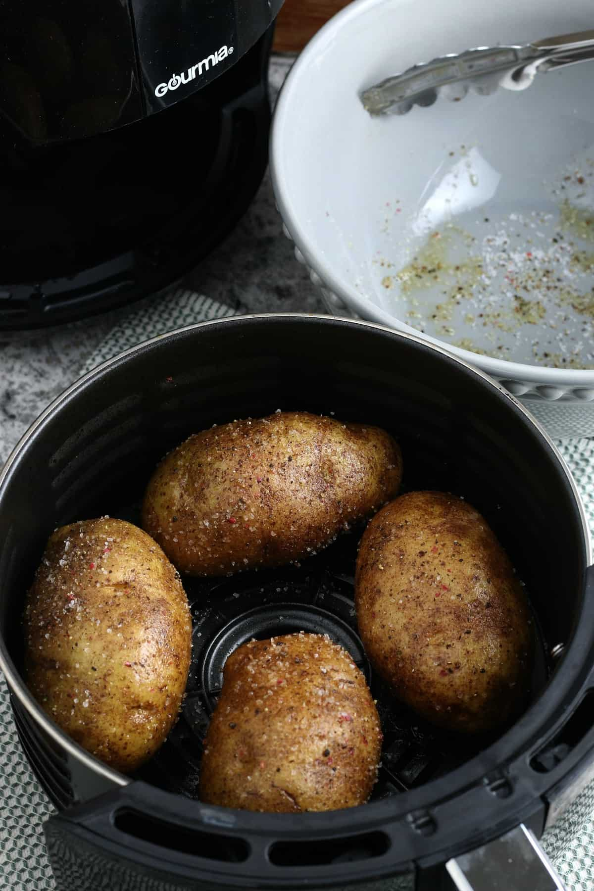 Looking down at four prepared baked potatoes in an air fryer basket with an empty bowl of oiled seasonings on the side.