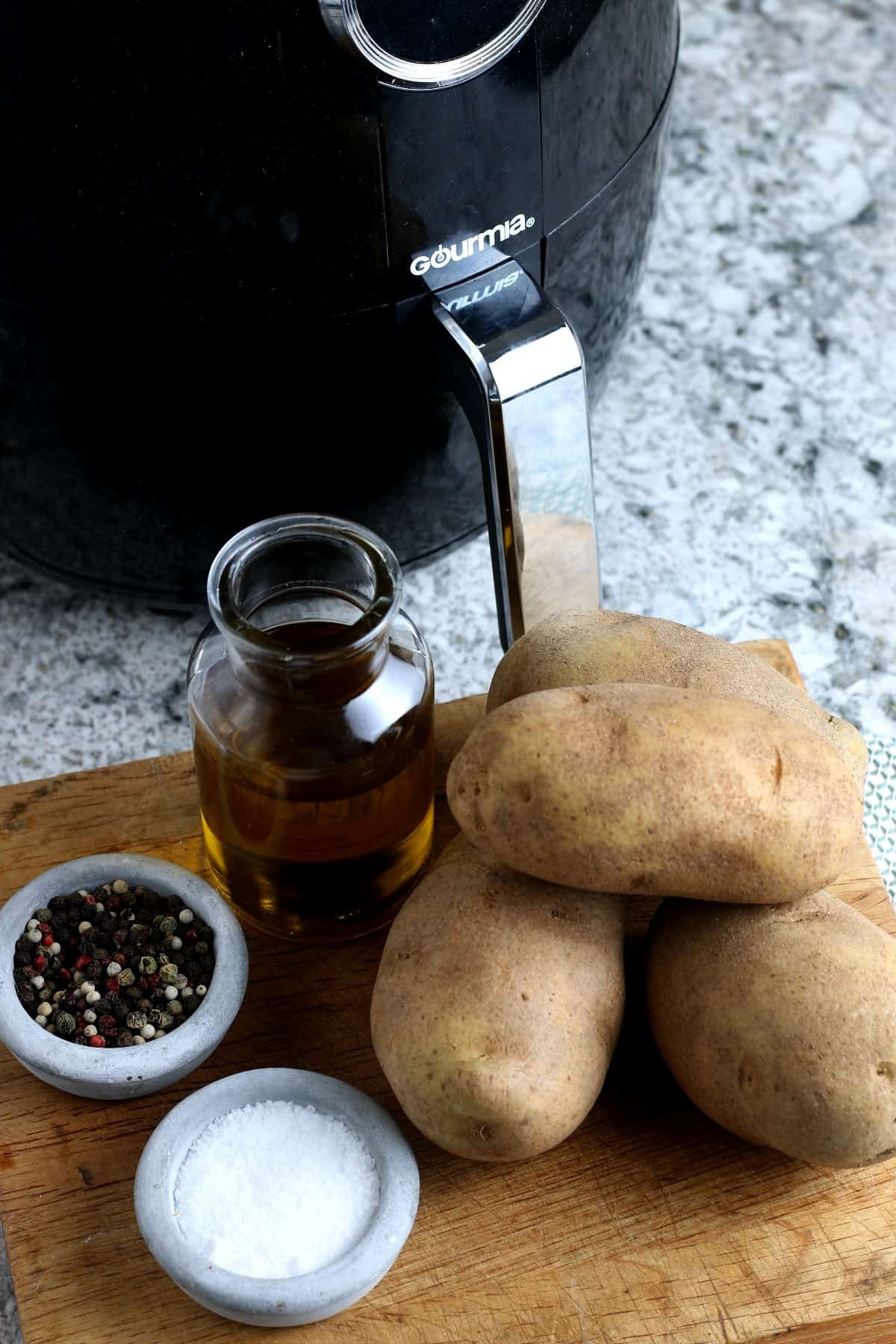Four simple ingredients including potatoes and olive oil sitting on a cutting board in front of an air fryer.