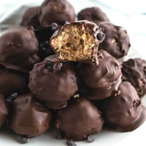Close up photo of a pile of chocolate balls with a bite out of the top front one so show the rice Krispie treat inside.