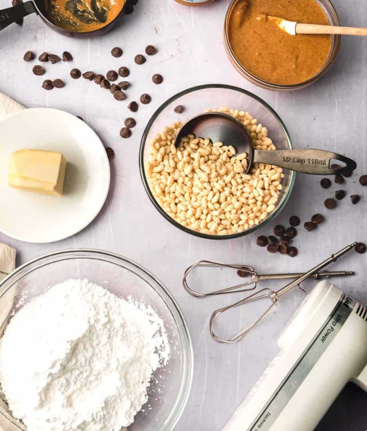 Overhead photo of ingredients for rice krispie peanut butter balls with a mixer and chocolate scattered around.