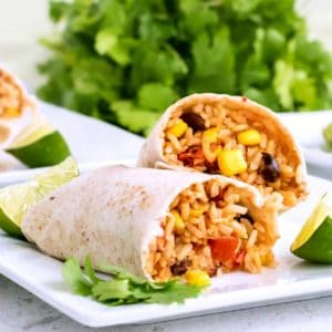 Two burritos are broken open and are overlapping each other to show the filling inside. All is on a white plate with limes and parsley arouns.