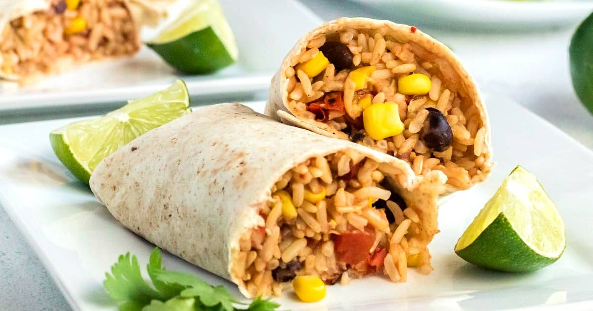 Two burritos cut in half to show the inside filling with rice and other goodies. Sitting on a white plate with limes on the side and another plate behind.