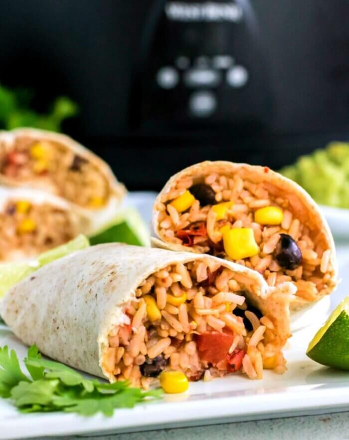 Two open vegan black bean burritos are overlapping each other on a white plate with a slow cooker in the background.