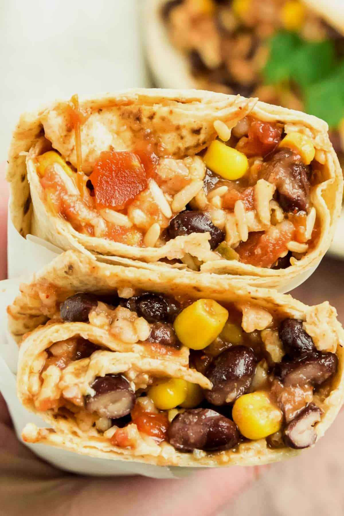 Two open vegan black bean burritos are being help up close to the camera in a hand and you can clearly see the delicious bean and rice filling.