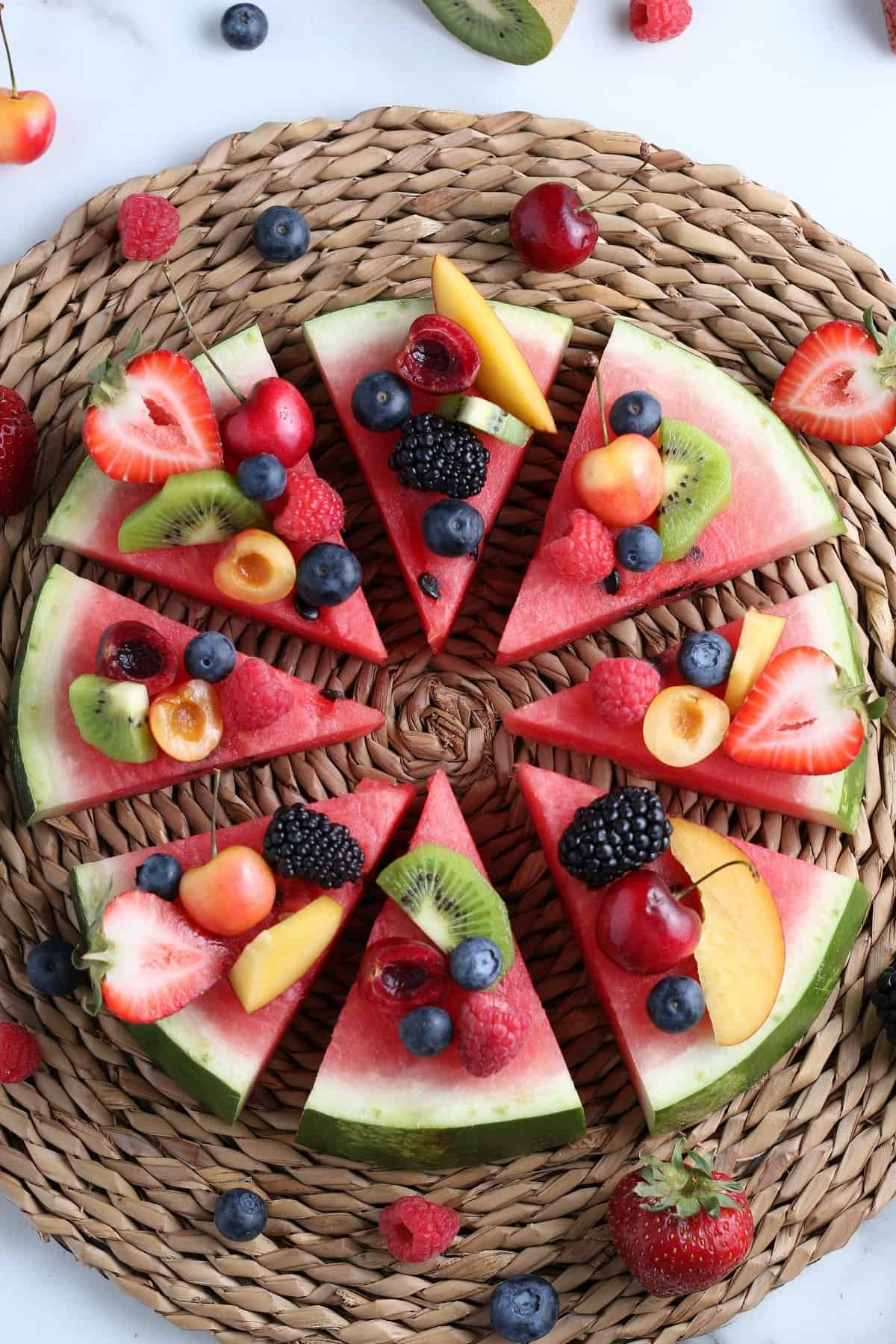 Overhead of sliced red melon round covered with berries and more and then sliced into wedges for serving.