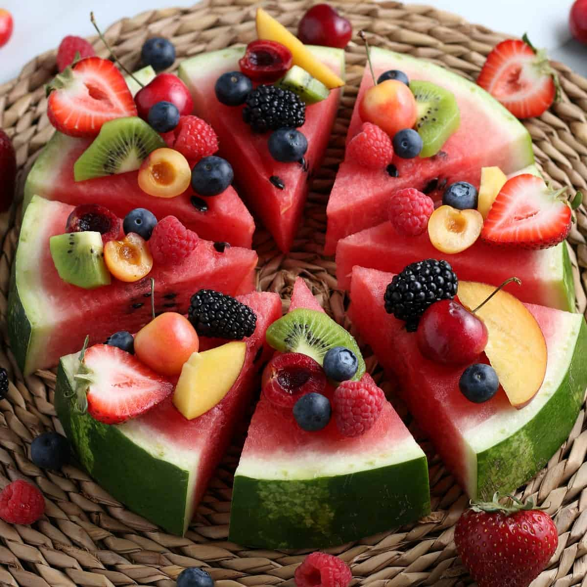 Angled thick slice of watermelon covered with fresh fruit pieces and then sliced into wedges for serving.