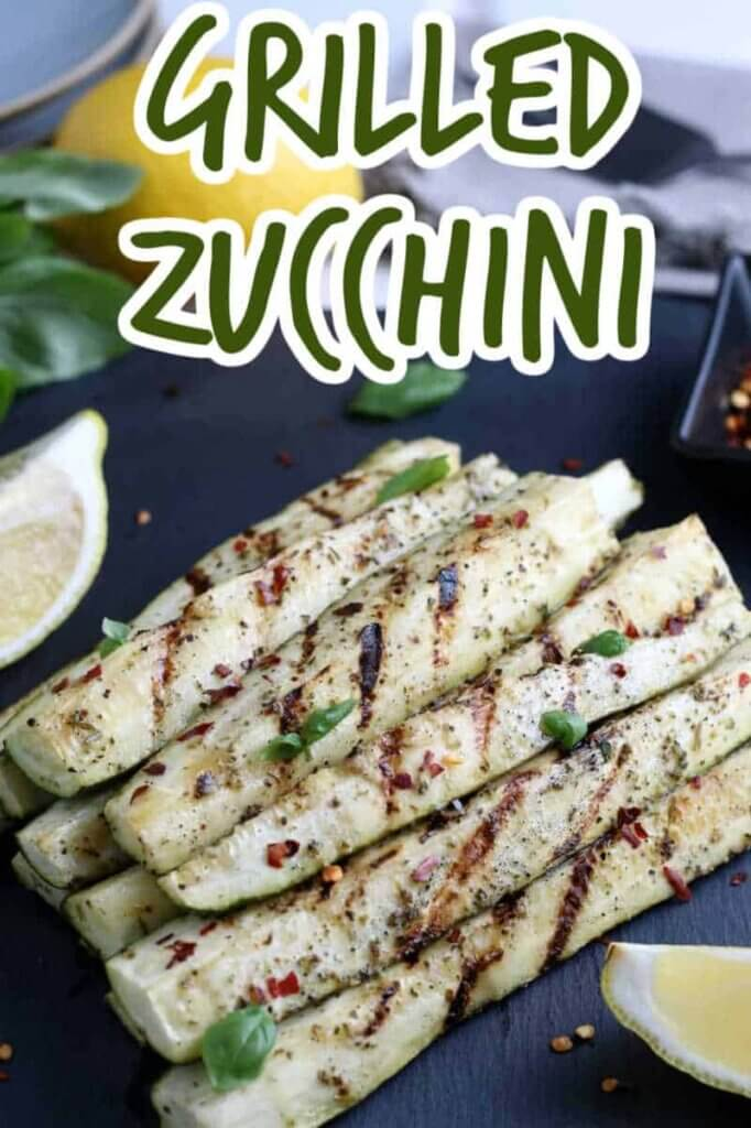 Closeup photo of grilled zucchini spears stacked in a pyramid with lemon wedges on the side. Text above.