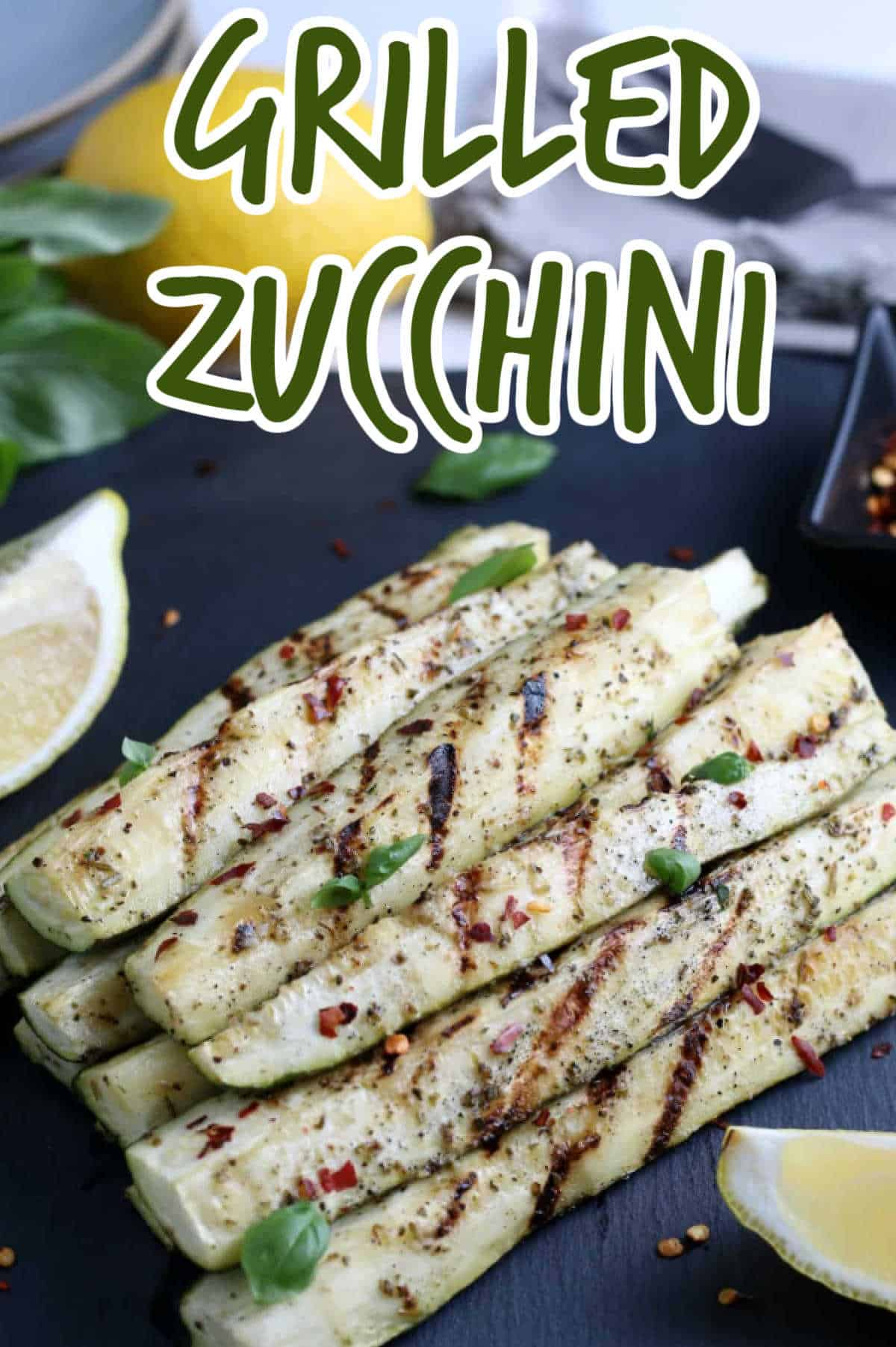 Closeup photo of grilled zucchini spears stacked in a pyramid with lemon wedges on the side. Text above