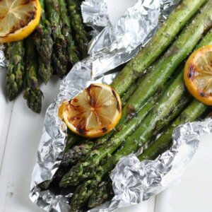 Close up photo of two open foil packets filled with grilled asparagus and grilled lemon slices.