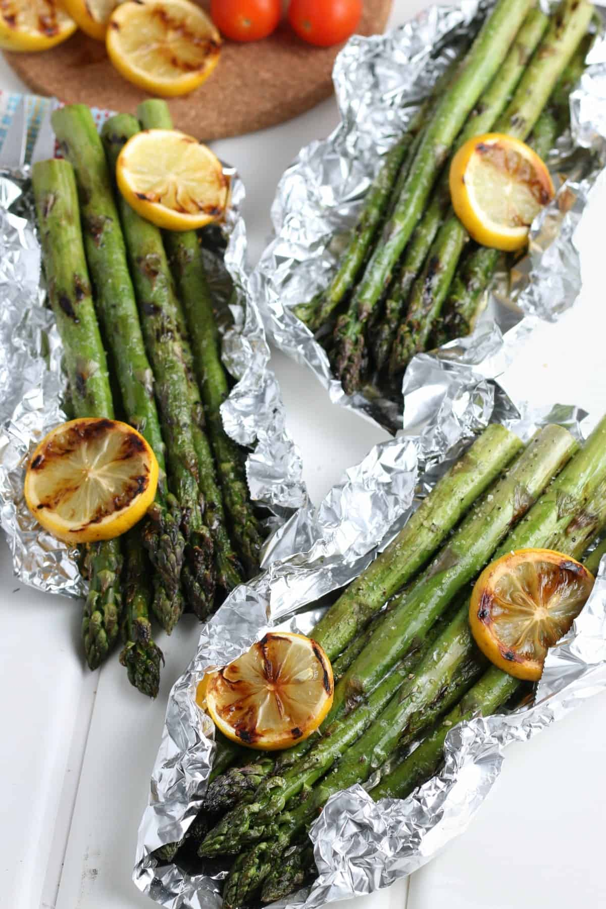 Overhead view of asparagus bundles in thier own foil packet with grilled lemon slices laying here and there.