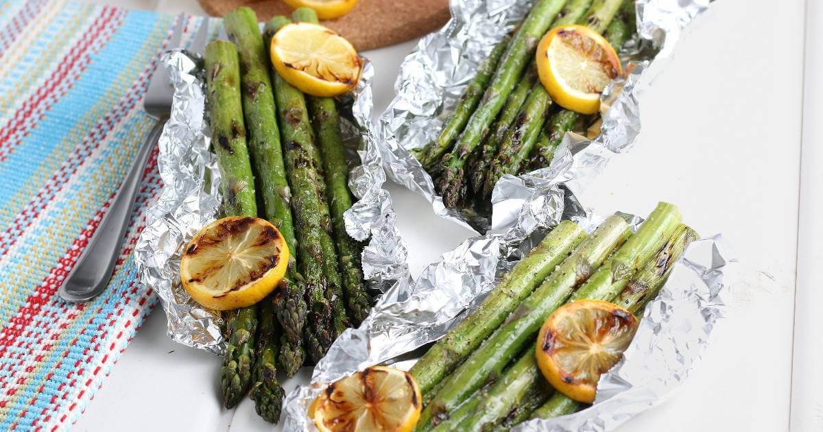 Wide photo with three grilled asparagus in foil packets laying open with grilled lemon slices and a colorful mat on the side.