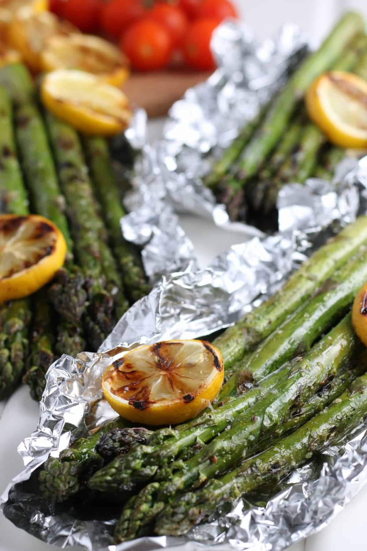 Closeup view of bundles of asparagus in open foil packets with grilled lemon slices laying alongside.